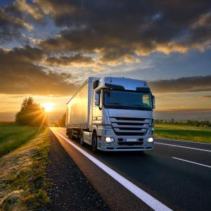 Truck at Dusk Countryside Two-lane, clouds and sun at the horizon AdobeStock_175552045.jpeg
